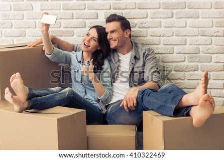 Happy attractive young couple is moving, making a selfie, cuddling and smiling while sitting among cardboard boxes - stock photo