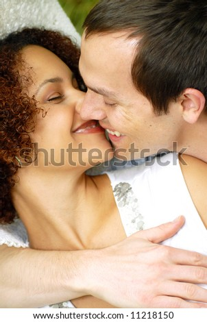 Happy, attractive young couple kissing in the park on a warm summer day