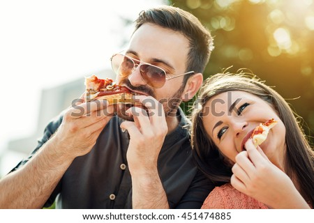 Happy attractive young couple romantically eating a fresh pizza outdoors. - stock photo