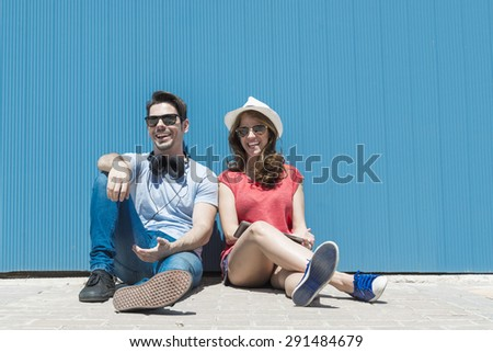 Happy attractive young couple sitting and laughing against a blue wall - stock photo