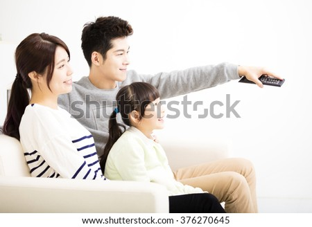 Happy Attractive Young  Family watching the tv - stock photo