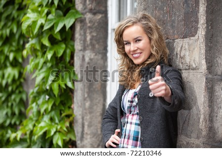 Happy attractive young female smiling and showing thumb - stock photo