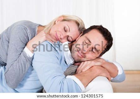 Happy attractive young man and woman smiling and cuddling as he relaxes on the sofa - stock photo