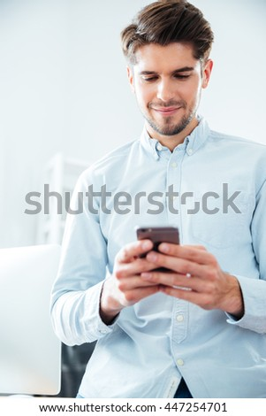 Happy attractive young man standing and using smartphone in office - stock photo