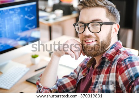Happy attractive young man with beard in glasses working and designing project on his computer  - stock photo