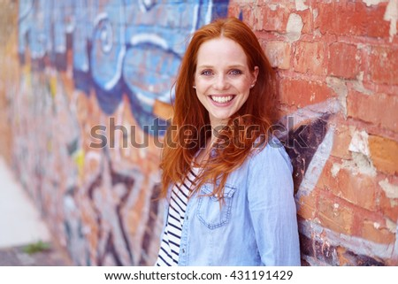 Happy attractive young woman posing against a graffiti covered brick wall outdoors looking at the camera with a vivacious smile - stock photo