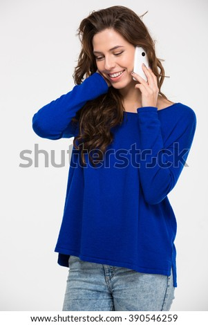 Happy attractive young woman standing and talking on mobile phone over white background - stock photo
