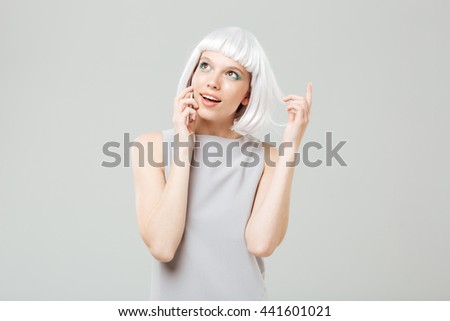 Happy attractive young woman talking on cell phone over white background - stock photo