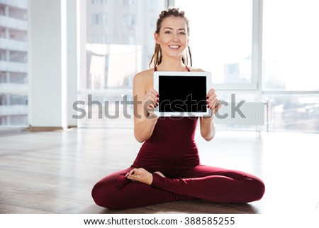 Happy attractive young woman with dreadlocks sitting in yoga pose and showing blank screen tablet - stock photo