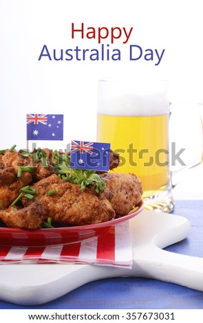 Happy Australia Day barbeque setting with spicy chicken wings with red, white and blue color theme with glass of beer.  - stock photo