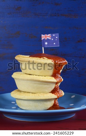 Happy Australia Day January 26 party food with iconic meat pies and tomato sauce on dark red and blue vintage rustic recycled wood background. - stock photo