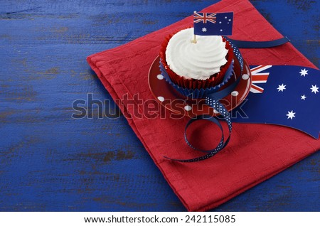 Happy Australia Day, January 26, theme table setting with red, white and blue cupcake on red polka dot plate and Australian flag decoration on dark blue wood background. - stock photo
