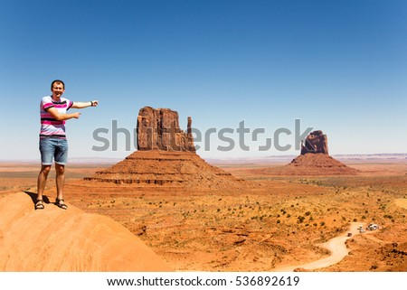 happy authentic young man at the picturesque Monument valley. Chill and happy! Truly delighted.
