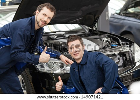 Happy auto mechanics. Cheerful young mechanics gesturing while standing in front of the car and smiling at camera - stock photo