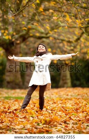 Happy autumn woman at the park with arms open - stock photo