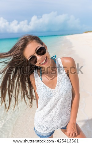 Happy aviator sunglasses woman beach fun playful with healthy hair. Beautiful young Asian model posing smiling at camera enjoying summer holidays on tropical destination on Caribbean travel. - stock photo