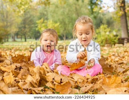 Happy baby and little girl have fun with autumn leaves in the park. - stock photo