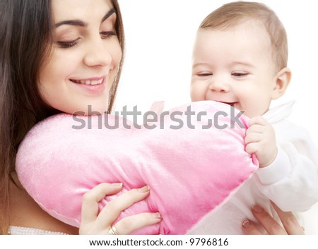 happy baby and mama with heart-shaped pillow - stock photo