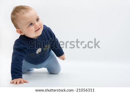happy baby boy crawling on bright background - stock photo
