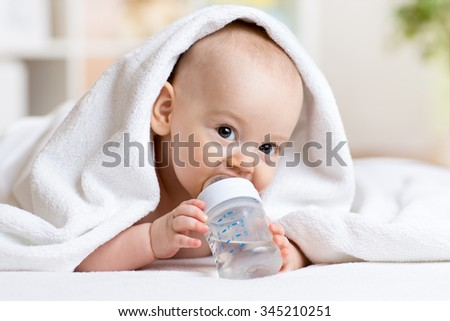 Happy baby boy drinks water from bottle wrapped towel after bath - stock photo