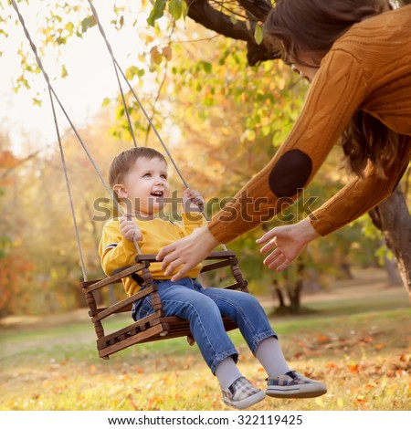 Happy baby boy having fun on a swing ride at a garden a autumn day - stock photo