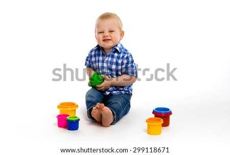 Happy baby boy in a plaid shirt with toys. studio - stock photo