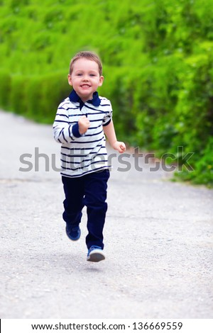 happy baby boy in motion, running the spring street - stock photo