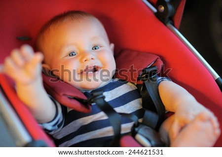 Happy baby boy in stroller  - stock photo