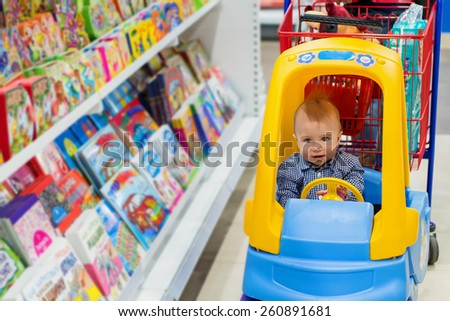 Happy baby boy in the little toy-car trolley in the kids shop in the bookstore department - stock photo