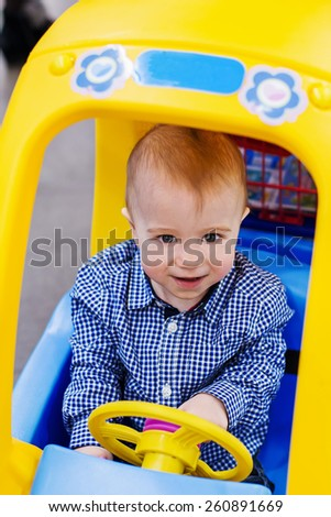 Happy baby  boy is driving, the little toy-car trolley - stock photo
