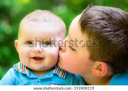 Happy baby boy kissed by his older brother - stock photo