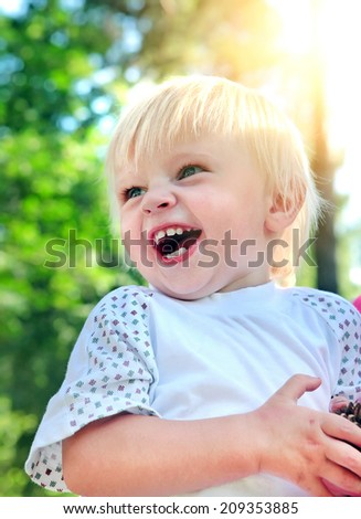 Happy Baby Boy laughing at the Summer Park - stock photo