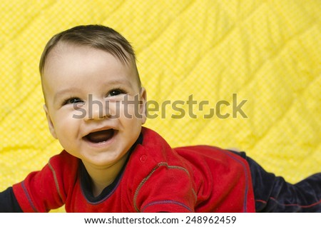 Happy baby boy laughing. Baby lying on his tummy laughing showing his first teeth. - stock photo