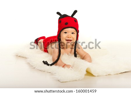 Happy baby boy laying and wearing funny ladybug hat - stock photo