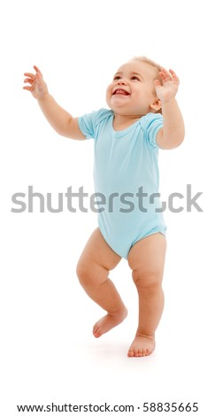 Happy baby boy looking up and walking with raised arms