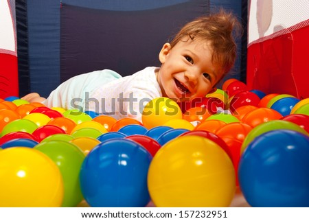 Happy baby boy lying on colorful balls in playpen - stock photo