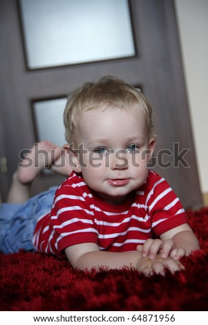 happy baby boy lying prone on a fur, red carpet in a modern room - stock photo