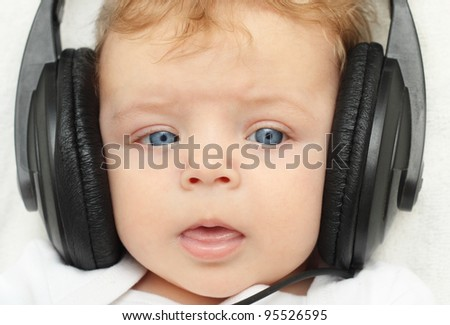 Happy baby boy 3 month old in earphones babbling - stock photo