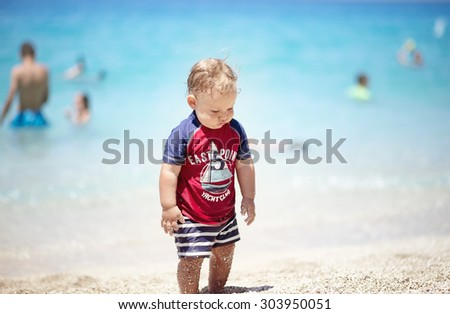 Happy baby boy on beautiful beach wearing protective suit - stock photo