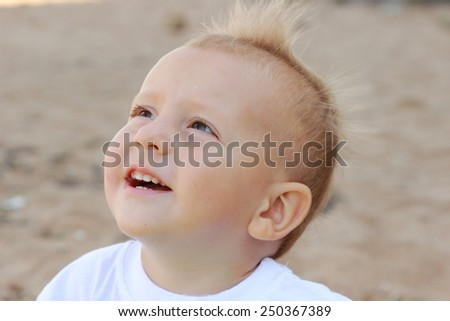 Happy baby boy on the beach by the sea - stock photo