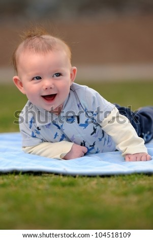 Happy Baby Boy Outside on Blanket. Smiling three-month old baby boy laying on a blue blanket outside. Shallow DOF. - stock photo