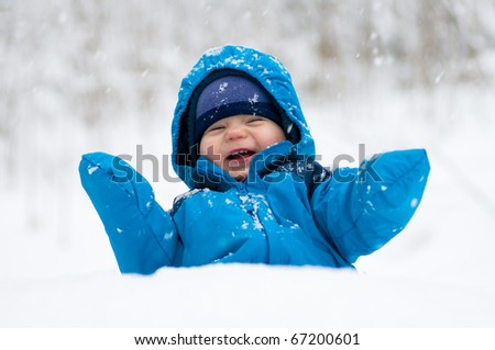 Happy baby boy playing in the snow - stock photo