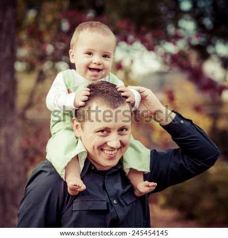 Happy baby boy riding his father's shoulders at park in filtered image  - stock photo