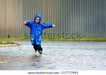 happy baby boy running the street, rainy weather - stock photo