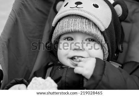 happy baby boy sitting in a stroller for a walk ( black and white ) - stock photo