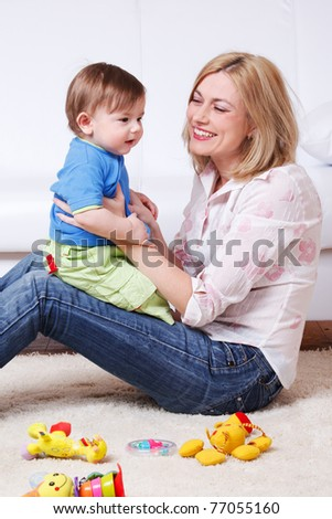 Happy baby boy sitting on mother's knees - stock photo