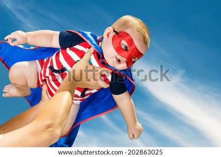 Happy baby boy wearing superhero costume flying in the sky - stock photo