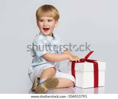 Happy baby boy with a gift box - stock photo