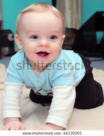 Happy baby boy with blonde hair and blue eyes crawls on floor with huge grin on his cute little face - stock photo