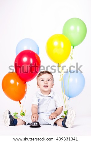 Happy baby boy with bunch of balloons isolated on white